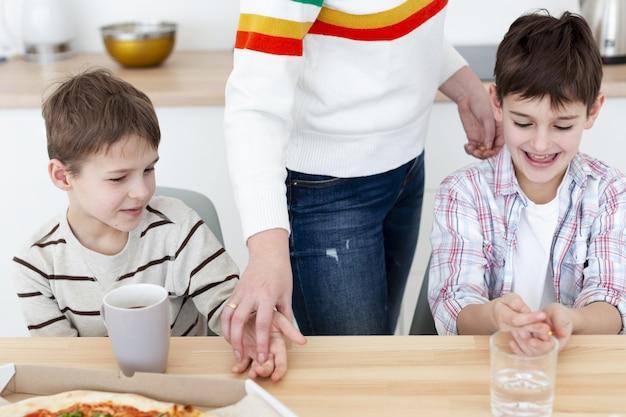Hoher winkel der kinder, die ihre hände desinfizieren, bevor sie pizza essen