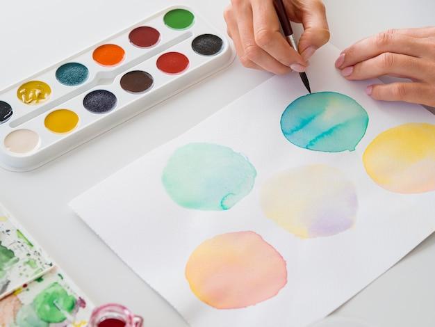 Hoher winkel der künstlermalerei mit pinsel und aquarell