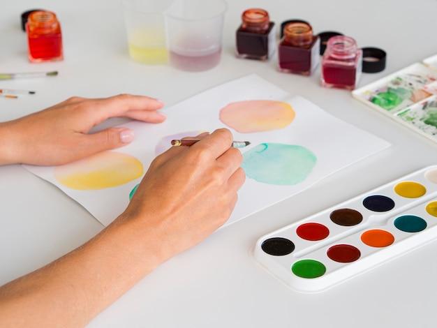 Hoher winkel der künstlermalerei unter verwendung des aquarells auf papier