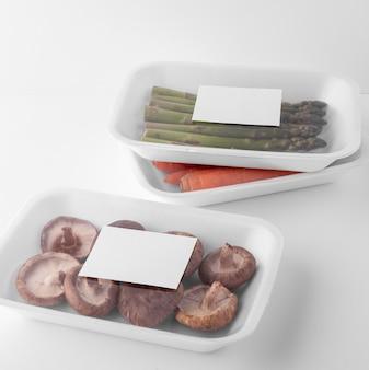 Hoher winkel der kunststoffverpackung mit pilzen, spargel und karotten