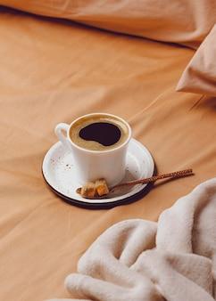 Hoher winkel der morgendlichen kaffeetasse auf dem bett