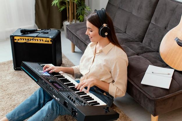 Hoher winkel der musikerin, die klaviertastatur spielt