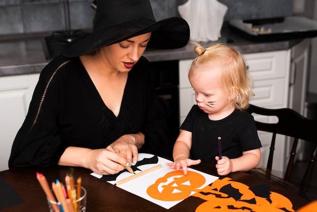 Hoher winkel der mutter und des kindes mit halloween-elementen