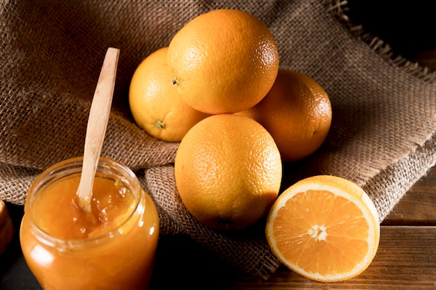 Hoher winkel der orangenmarmelade im glas mit früchten