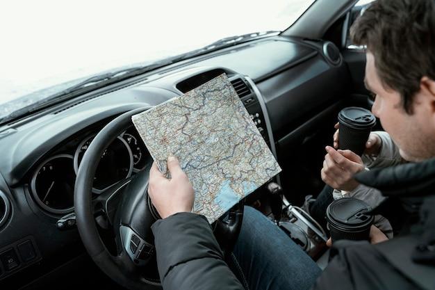 Hoher winkel der paarberatungskarte im auto während einer straßenreise
