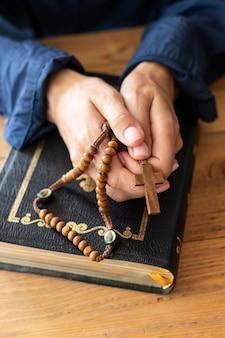 Hoher winkel der person, die mit rosenkranz und kreuz betet