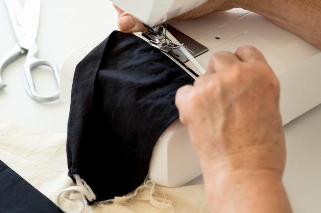 Hoher winkel der person mit nähmaschine für gesichtsmaske