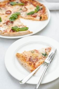 Hoher winkel der pizzascheibe auf einer platte auf normalem hintergrund