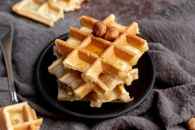 Hoher winkel der platte mit den waffeln überstiegen mit honig und haselnüssen