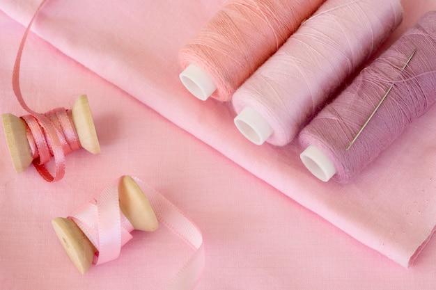 Hoher winkel der rosa fadenrollen mit band und textil