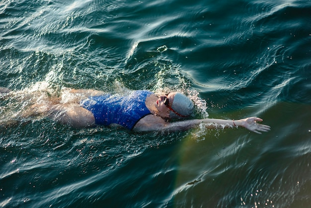 Hoher winkel der schwimmerin mit mütze und schutzbrille, die im wasser schwimmen
