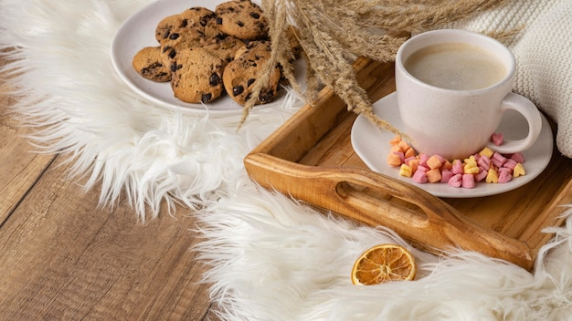 Hoher winkel der tasse kaffee mit keksen und getrockneten blumen