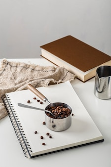 Hoher winkel der tasse mit kaffeebohnen auf notizbuch
