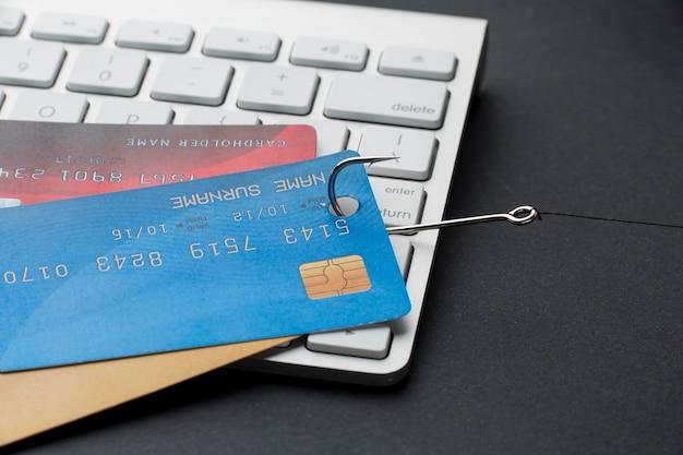 Hoher winkel der tastatur mit kreditkarten und haken für phishing