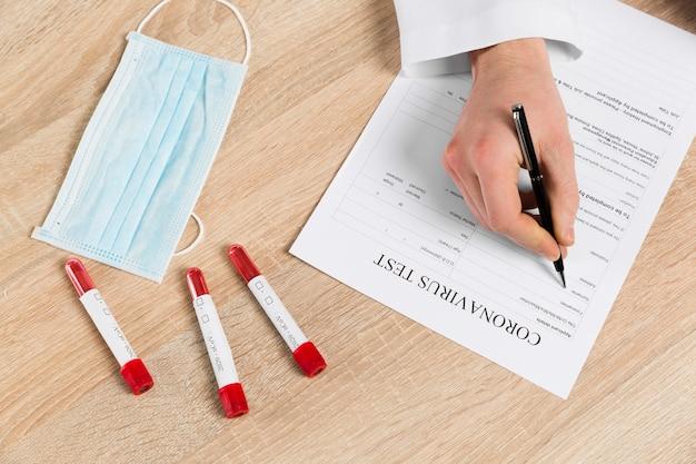Hoher winkel des arztes beim ausfüllen des coronavirus-tests