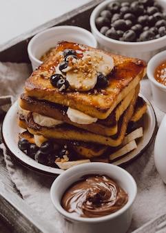 Hoher winkel des frühstückstoasts mit banane und blaubeeren