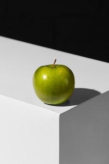 Hoher winkel des grünen apfels auf dem podium