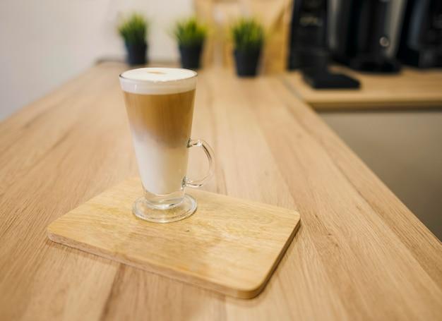 Hoher winkel des kaffeegetränks serviert auf holzteller