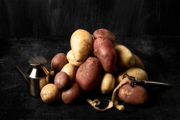 Hoher winkel des kartoffelhaufens mit schäler