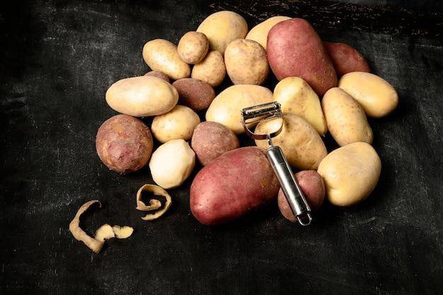 Hoher winkel des kartoffelstapels mit schäler