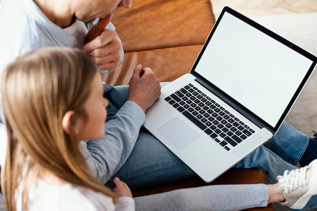 Hoher winkel des kleinen mädchens und ihres vaters verbringen zeit auf laptop
