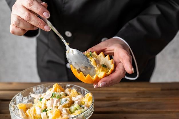 Hoher winkel des kochs, der orange mit gericht füllt