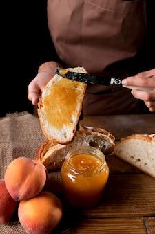 Hoher winkel des kochs, der pfirsichmarmelade auf brot verteilt