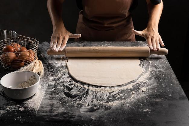 Hoher winkel des kochs, der teig mit mehl rollt