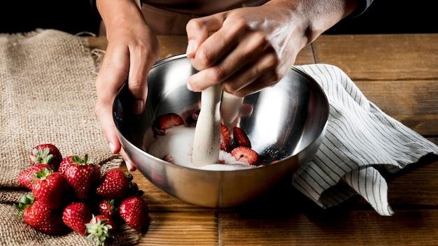 Hoher winkel des küchenchefs, der erdbeeren und zucker in der schüssel mischt