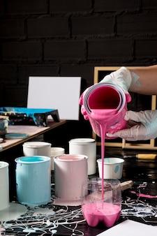 Hoher winkel des künstlers, der rosa farbe von der dose gießt
