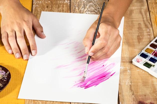 Hoher winkel des künstlers in der studiomalerei auf papier