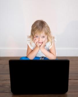 Hoher winkel des mädchens, das auf laptop schaut