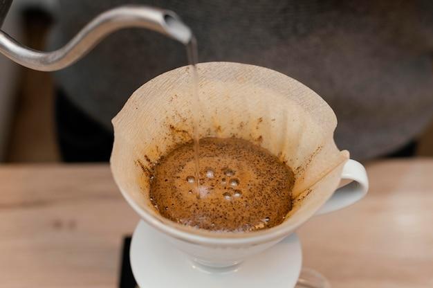 Hoher winkel des männlichen barista, der heißes wasser über kaffeefilter gießt