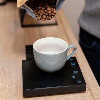 Hoher winkel des männlichen barista, der kaffeebohnen unter verwendung der skala gewichtet