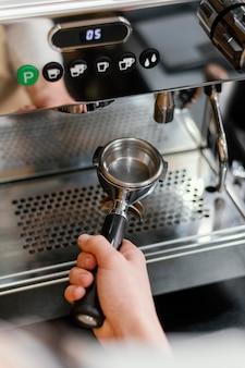 Hoher winkel des männlichen barista mit kaffeemaschine