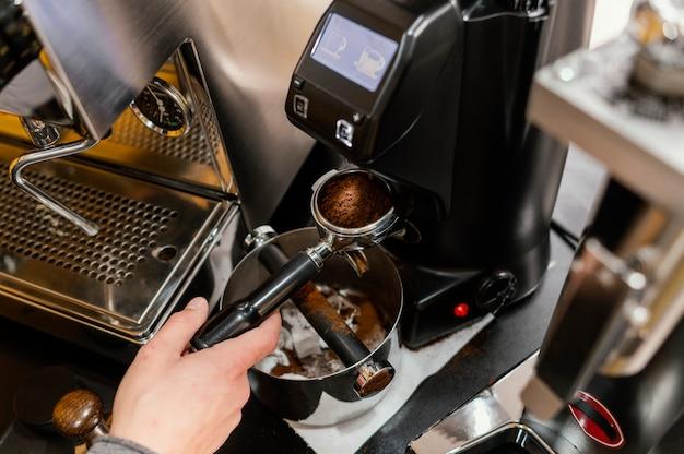 Hoher winkel des männlichen barista mit professioneller kaffeemaschine