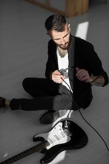 Hoher winkel des männlichen künstlers, der e-gitarre spielt