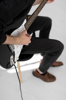 Hoher winkel des männlichen musikers, der e-gitarre spielt