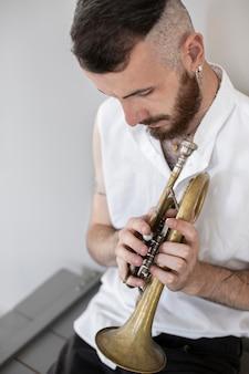 Hoher winkel des männlichen musikers, der kornett spielt