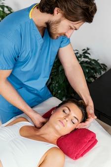 Hoher winkel des männlichen osteopathischen therapeuten, der die halswirbelsäule der patientin überprüft