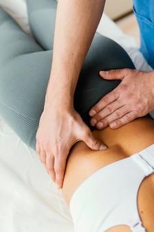 Hoher winkel des männlichen osteopathischen therapeuten, der die untere rückenwirbelsäule der patientin überprüft