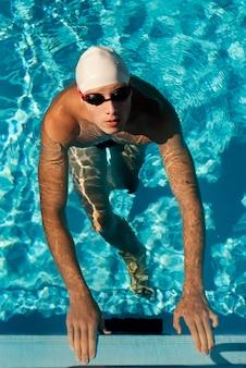 Hoher winkel des männlichen schwimmers, der aus dem pool herauskommt