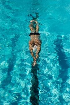 Hoher winkel des männlichen schwimmers, der im wasserbecken schwimmt