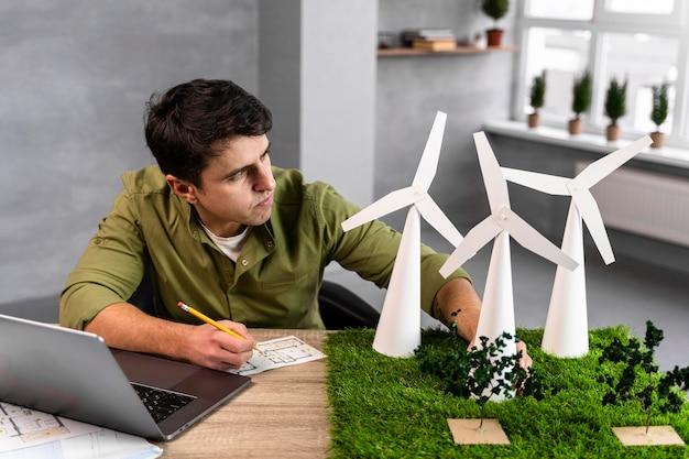 Hoher winkel des mannes, der an einem umweltfreundlichen windkraftprojekt arbeitet