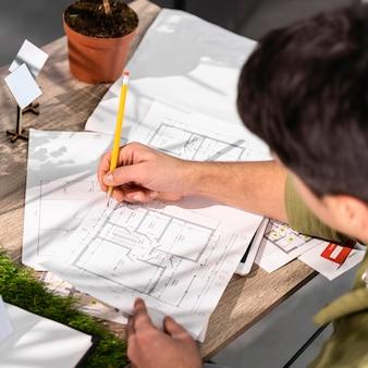 Hoher winkel des mannes, der an einem umweltfreundlichen windkraftprojekt mit papieren und bleistift arbeitet