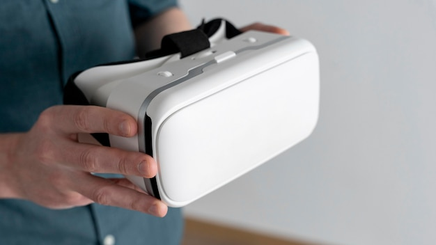 Hoher winkel des mannes, der virtual-reality-headset hält