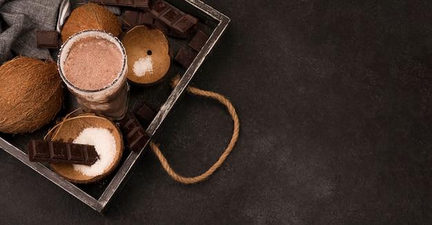 Hoher winkel des milchshake-glases auf tablett mit kokosnuss und schokolade