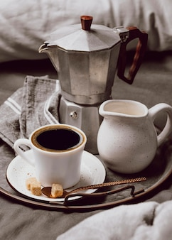 Hoher winkel des morgenkaffees auf dem bett mit milch und wasserkocher