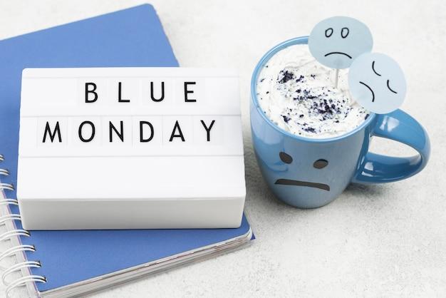 Hoher winkel des notizbuchs mit trauriger tasse für blauen montag