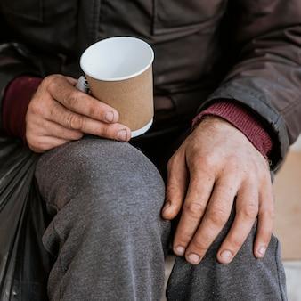 Hoher winkel des obdachlosen, der leere tasse hält